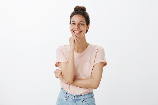Беззаботная молодая стильная женщина позирует у белой стены