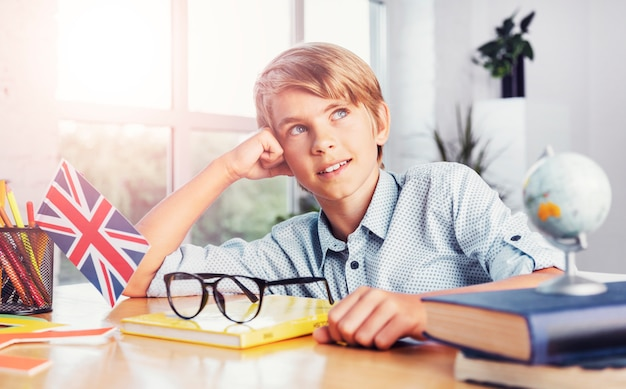 Carefree young thoughtful boy in classroom, learning english concept
