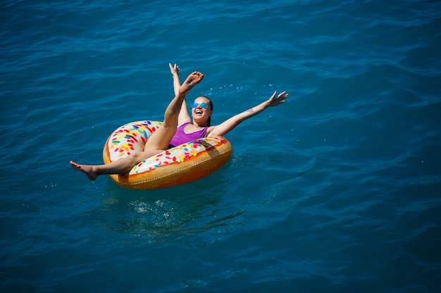 Carefree young woman enjoying a relaxing day at sea, floating on an inflatable ring. sea vacation concept