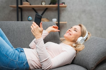 Carefree young woman enjoying the music on headphone holding mobile in hand