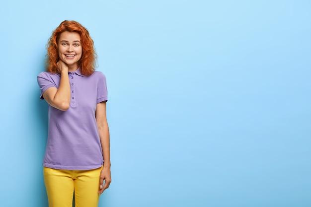 Беззаботная молодая женщина с короткими рыжими волосами позитивно улыбается