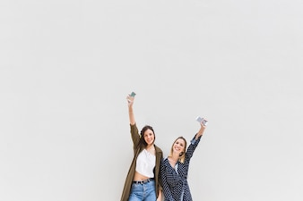 Carefree young woman holding cellphone raising their hands against white backdrop