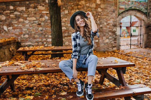 Беззаботная молодая женщина в модных винтажных штанах сидит на столе в парке и смеется