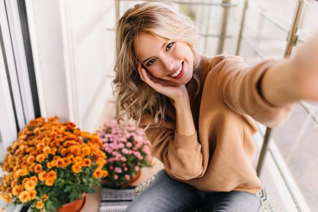 노란색 꽃 근처 selfie를 만드는 평온한 젊은 여자. 발코니에 앉아 귀여운 백인 여자입니다.