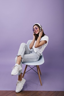Carefree young woman in trendy sneakers sitting on chair and listening music. fashionable brunette female model in headphones posing.