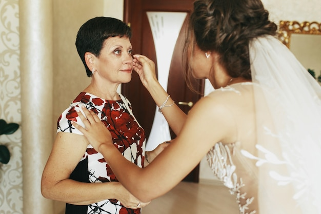 Careful bride takes somthing bride mother's face