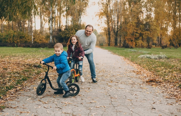 Careful caucasian father having a walk in the park with his kids teaching them to ride the bike