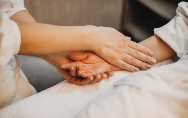 신중한 피부과 전문의가 고객의 손을 만지고 스파 절차를 준비합니다.