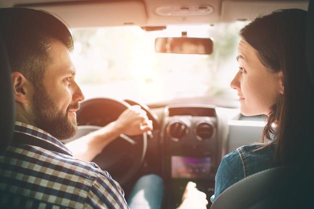 신중한 운전. 아름 다운 젊은 부부는 조수석에 앉아 잘 생긴 남자가 차를 운전하는 동안 웃 고.
