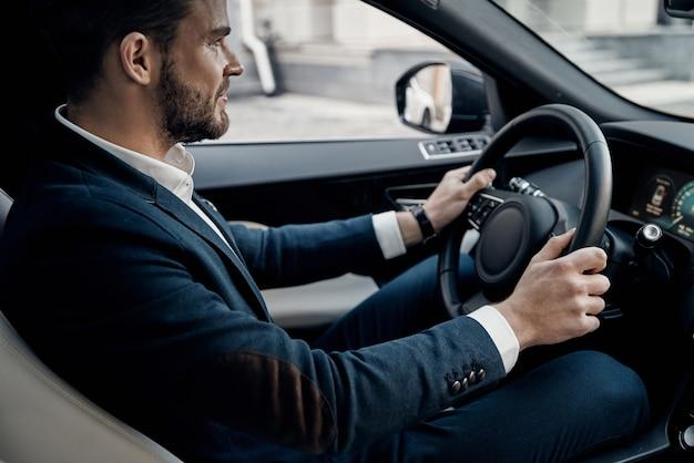조심 운전. 차를 운전하는 동안 똑바로보고 웃는 전체 양복에 잘 생긴 젊은 남자