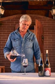 나무 테라스에 서있는 동안 병에서 디켄터에 적포도주를 붓는 신중한 숙련 된 와이너리 작업자