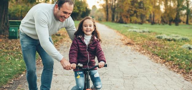 Заботливый отец учит свою дочь ездить на велосипеде, помогая ей в парке, улыбаясь