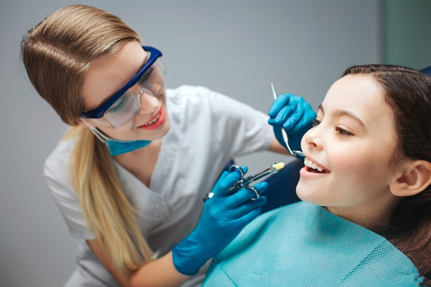 Careful female dentist hold tools close to girl mouth. child show front teeth. she sit calmly in dental chair.