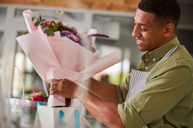 Careful florist putting a posy with a pink paper around it in a tiny package with blue handles