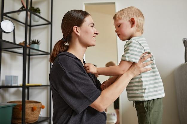 Заботливый маленький сын стоит перед беременной матерью и поправляет ее рубашку в коридоре