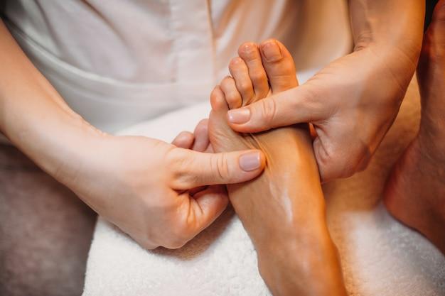 Массажист трогает ноги клиента во время спа-процедуры в салоне красоты