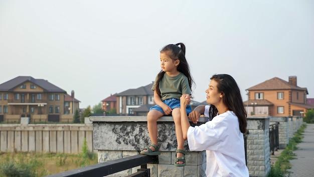 신중한 어머니는 일몰 시 현대 도시 제방의 큰 난간 받침대에 앉아 있는 아시아 소녀의 손을 잡고 있습니다.
