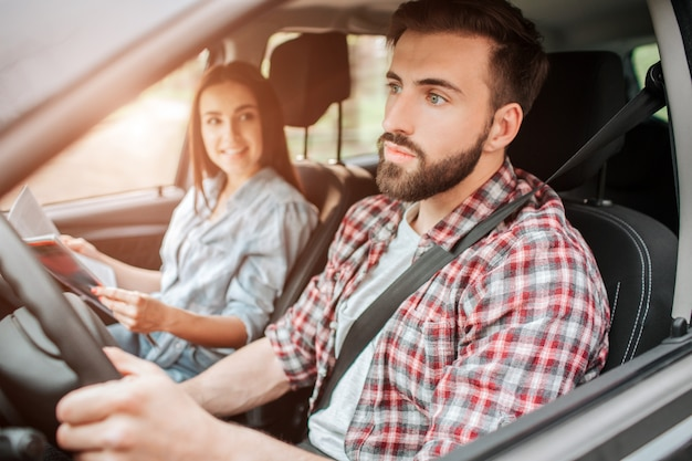 Careful and nice guy is driving car and looking straight forward. he is paying all of his attention to the road. girl is sitting besides him.