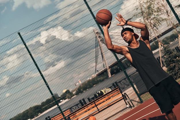注意深い撮影。屋外でバスケットボールをしながらボールを投げるスポーツウェアの若いアフリカ人