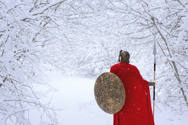 Careful spartan in cold snowy forest