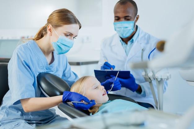 注意深い監督。プロの歯科医の監修のもと、口腔内検査を行う快活な医学生