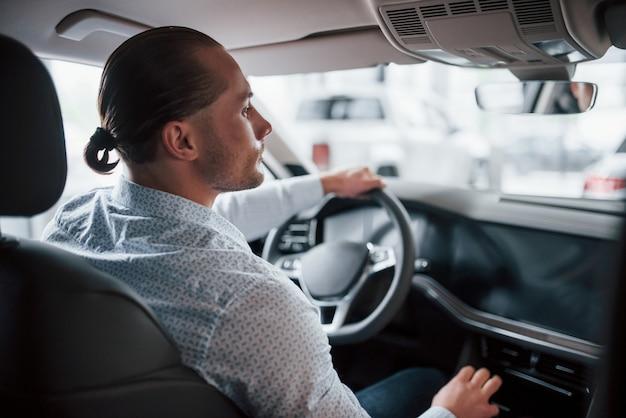 Осторожно с вождением. мужчина пробует новую машину в салоне в дневное время. покупка нового автомобиля