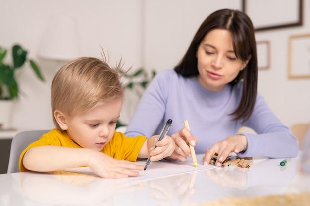 Заботливая молодая мать сидит за столом и рисует на бумаге с маленьким сыном