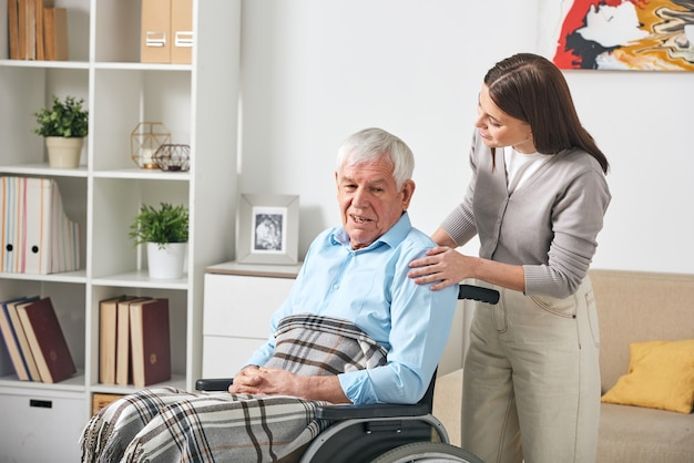 Careful young nurse talking to elderly man in wheelchair while visiting him at home
