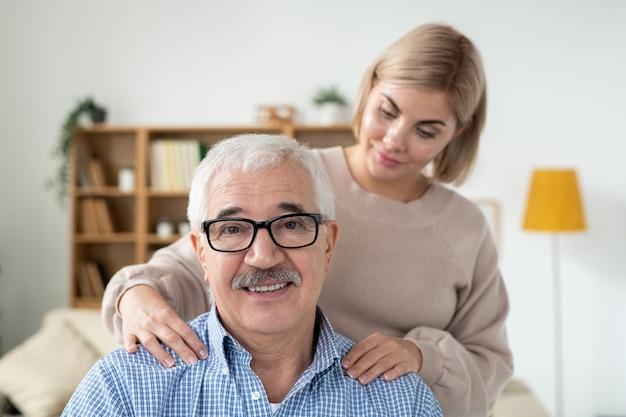 家庭環境で笑顔でカメラを見て彼女のシニアの父親に肩のマッサージをしている慎重な若い女性