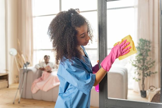 간병인 청소. 환자의 집에서 유리문을 청소하는 곱슬 아프리카 계 미국인 간병인