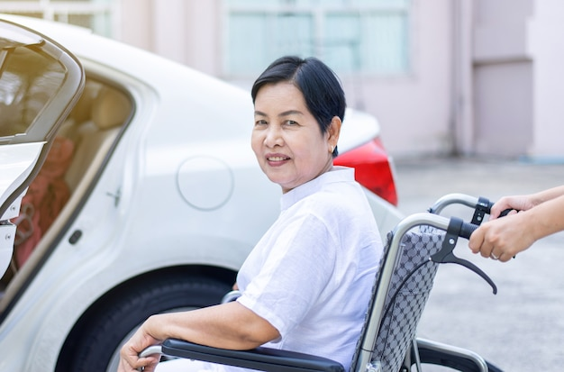 Caregiver helping senior handicapped asian woman from wheelchair get into car