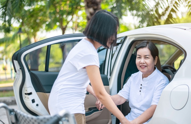 Caregiver helping senior handicapped asian women from wheelchair get into car