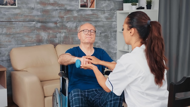 Caregiver helping senior man in wheelchair with physical thepray. disabled handicapped old person recovering professional help nurse, nursing retirement home treatment and rehabilitation