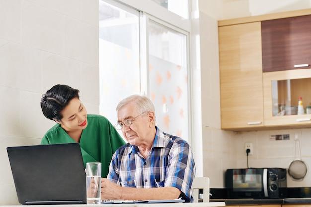 Воспитатель, помогающий старшему мужчине с вычислениями