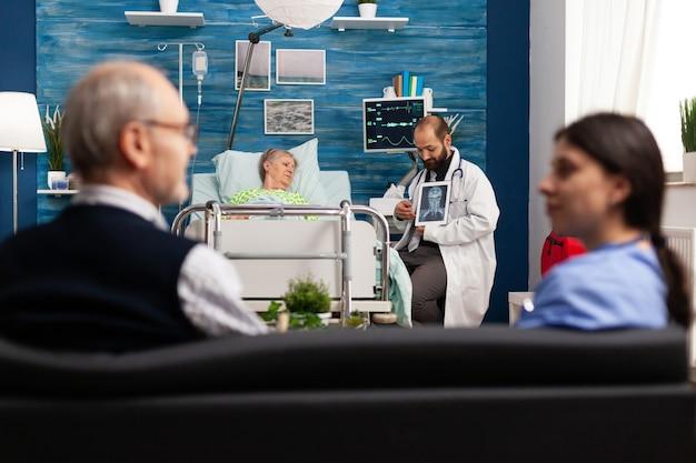 병든 은퇴한 노년 여성과 질병 치료에 대해 논의하는 방사선 사진을 설명하는 간병인 남자 의사. 사회 서비스 간호 노인 은퇴 여성. 의료 지원