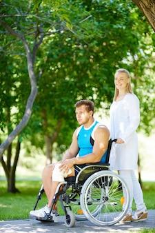 간병인 휠체어 야외에서 젊은 환자를 밀고