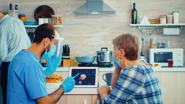 在宅訪問中に高齢患者とコロナウイルスについて話し合う介護者ソーシャルワーカー。高齢の退職した女性の男性看護師がcovid-19の広がりを説明し、リスクグループの人々を助けます