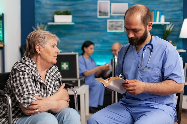 Caregiver support nurse reading book stories to senior disabled pensioner
