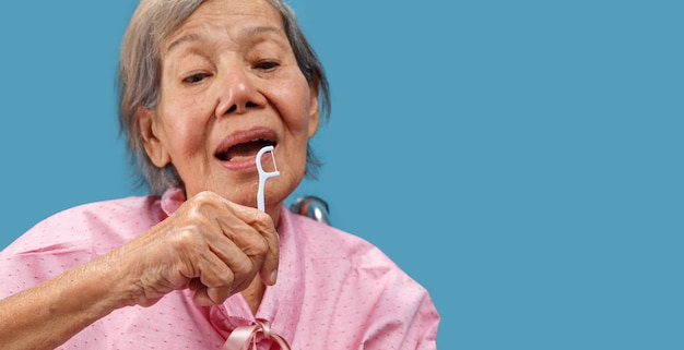 Caregiver take care asian elderly woman while using dental fross stick.