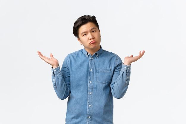 Uomo asiatico incurante senza emozioni, imbronciato come alzando le mani e alzando le spalle, non sa nulla, non importa, essere inconsapevole e all'oscuro, non ha risposte, in piedi su sfondo bianco.