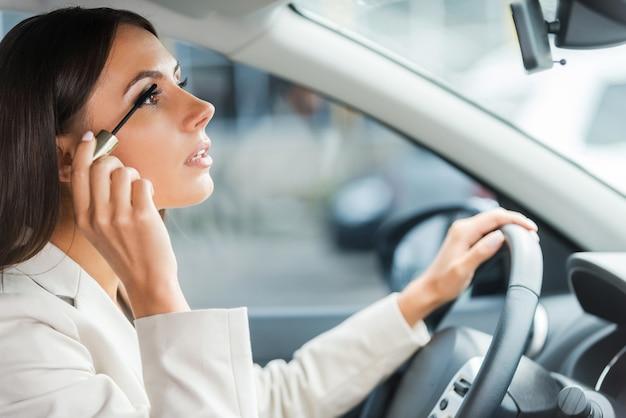 부주의 한 운전자. 차를 운전하는 동안 화장을하는 formalwear에서 젊은 여자의 측면보기