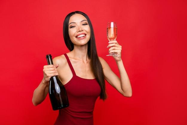 Беззаботная модная брюнетка с напитком в руке изолирована на красной стене