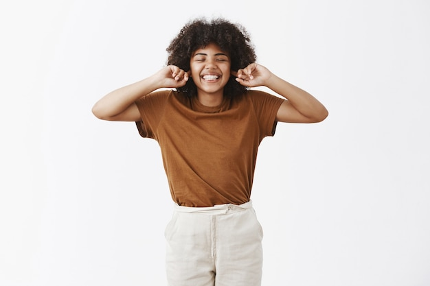 Careless and happy attractive dark-skinned woman with curly hair in stylish outfit closing eyes and smiling with carefree indifferent expression covering ears with index fingers