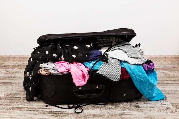 黒のスーツケースに服を不注意に梱包