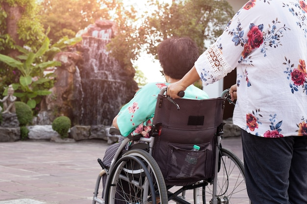 Caretaker with patient outdoor in wheelchair for fresh air