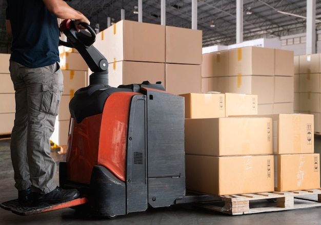 Cargo boxes shipment. worker working with electric forklift pallet jack unloading cardboard boxes at the warehouse.