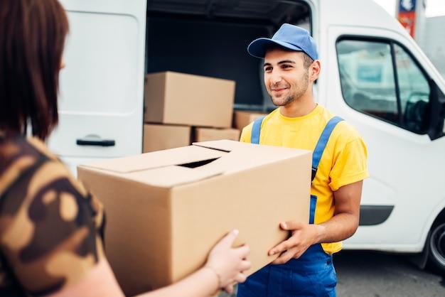 Служба доставки грузов, мужской курьер в униформе выдает посылку клиенту, дистрибьюторский бизнес. грузовик с картонными посылками.