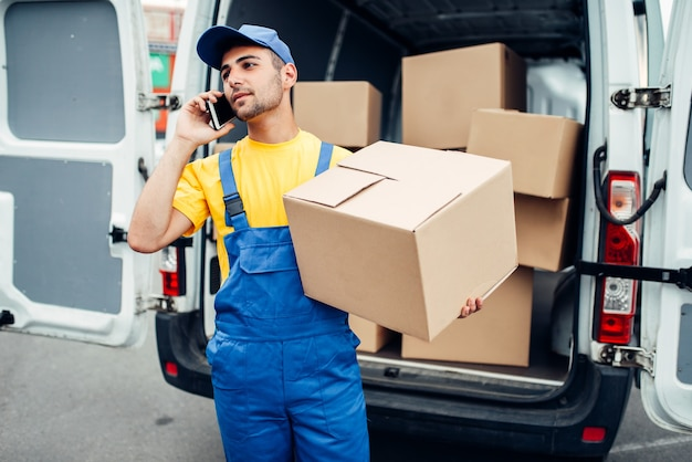 Служба доставки грузов, мужской курьер в форме с коробкой и мобильным телефоном в руках. пустой контейнер
