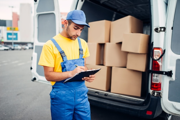 Cargo delivery service, male courier in uniform and truck with cardboard boxes.empty container