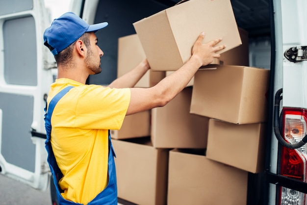 Cargo delivery service, male courier in uniform with box in hand unloads truck with cardboard parcels. empty container